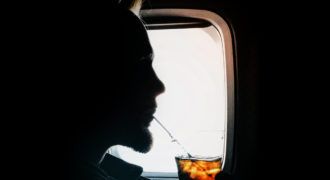 Silhouette of man drinking from a straw